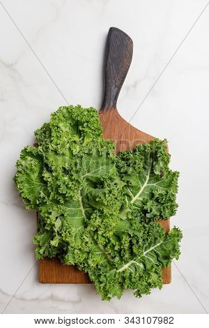 Kale On Cutting Board On White Marble Background. Concept Of Healthy Food