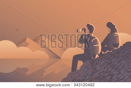 A Man And A Woman Travel Through The Wild With A Camera. Evening Landscape By The Lake With Mountain