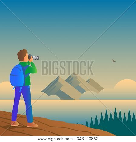 A Male Tourist With A Backpack Stands On A Mountain And Photographs Wildlife On A Camera. In The Dis