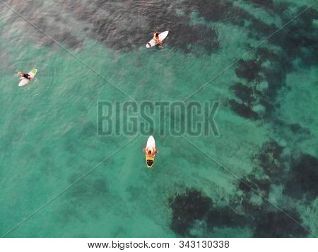 Aerial View Of Surfers Waiting The Waves In Blue Clear Water. Surfer On The Waves, Surfers On Their