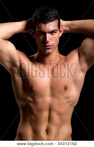 Healthy muscular young man. Isolated on black background.  Shallow DoF with focus on face.