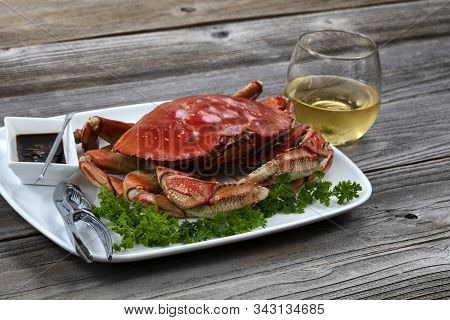 Whole Cooked Dungeness Crab In Dinner Table Setting With White Wine In Close Up Layout