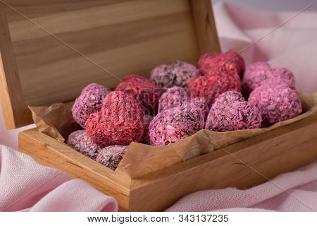 Heart Shaped Energy Bites For Valentine's Day In Wooden Box On Pink Cloth, Closeup