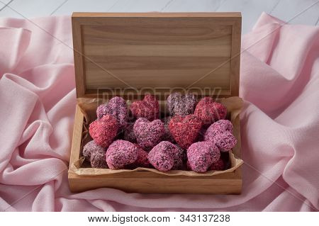 Heart Shaped Energy Bites For Valentine's Day In Wooden Box On Pink Cloth, Above View