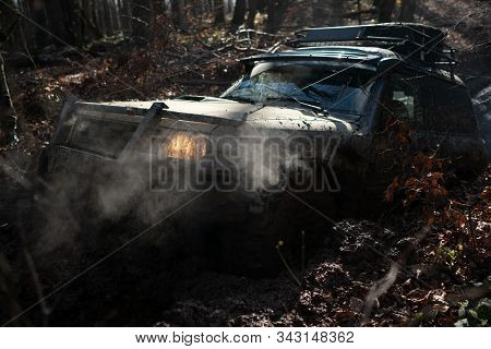 Jeep Crushed Into A Paddle And Picked Up A Spray Of Dirt. Off-road Sport Truck Between Mountains Lan