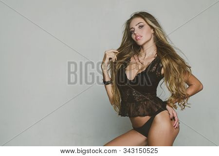 Sexy Hot Blonde Woman With Long Hair Wearing Black Luxury Lace Lingerie Isolated At Gray Background.