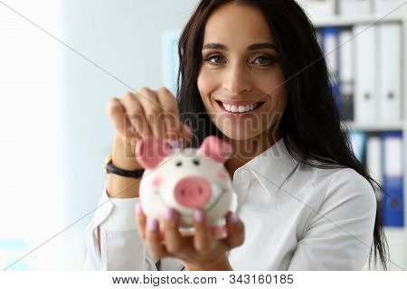 Portrait Of Beautiful Brunette Putting Saved Coin In Thrift-box. Wonderful Businesslady Looking At C