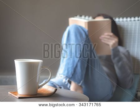 Asia Beautiful Woman In Blue Jeans And Turtleneck Reading Book With Beverage On Cozy Chair In Room W