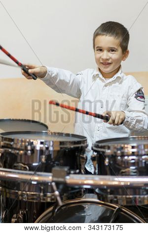 Boy Drumming. Boy In A White Shirt Plays The Drums. A Boy In A White Shirt Is Drumming. Vertical Pho