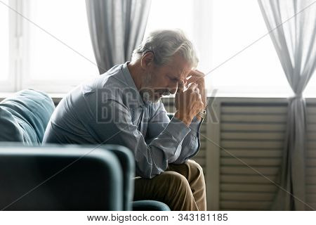 Seated On Couch Hunched Old Man Looking Desperate And Lonely