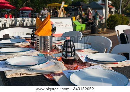 Darwin, Australia - June 1, 2019: Table Set For Dinner With White Plates And Orange Napkins At Malak