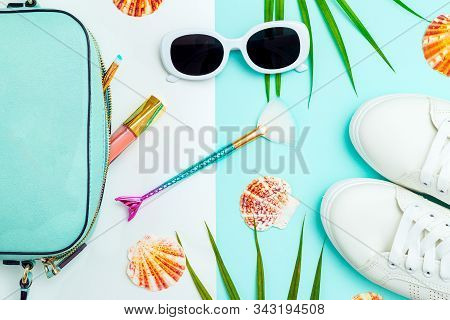 Travel Accessories. White Sneakers And White  Sunglasses On A Blue And White Background. Flat Lay