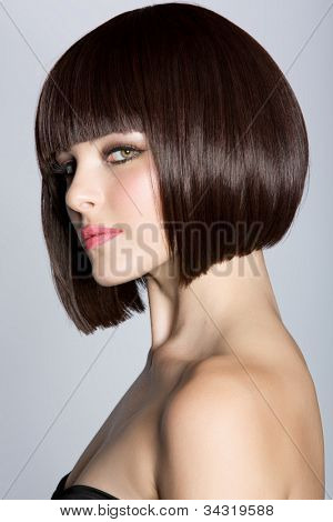 portrait of a beautiful woman in short brunette bob with neat clean hair on studio background