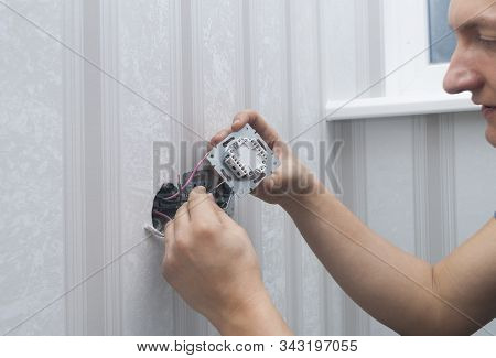 Electrician Installs Lighting Switch