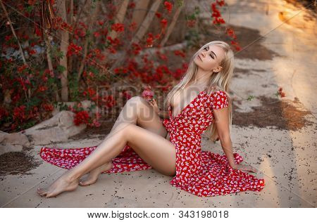 Woman In The Fluttered Red Dress Posing In The Garden Near The Red Blooming Bushes In The Rays Of Se