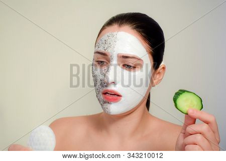 The Face Of The Woman With A Cosmetic Mask. The Concept Of Spa, Beauty And Skin Care. Cotton Disc An