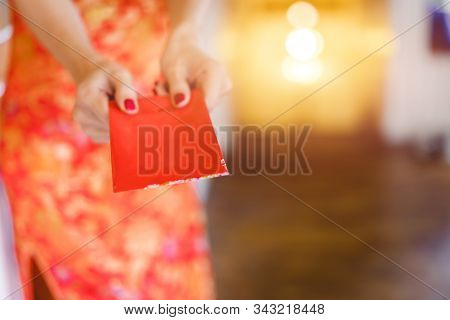 Hands Of Chinese Woman Wearing A Qipao Dress Traditional Or Cheongsam Giving A Red Envelope Or Ang P