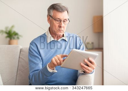 Serious Elderly Man Using Digital Tablet Browsing Internet And Reading Business News Sitting On Couc