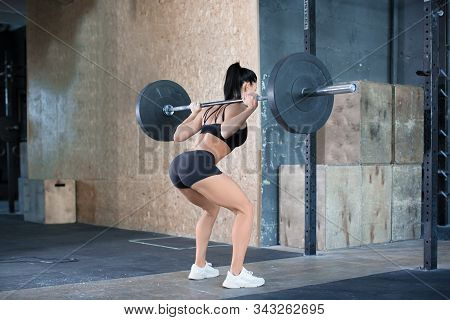 Side-back Photo Of A Woman Is Lifting Weight While Working Out With Barbell In Gym. Sport And Health