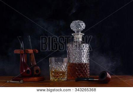 A Handsome Decanter And A Glass Of Whisky Next To The Smoking Pipes Stand On The Table Shrouded In T