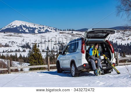 Woman Changing Boots To Ski Sitting In Car Trunk. Sunny Day