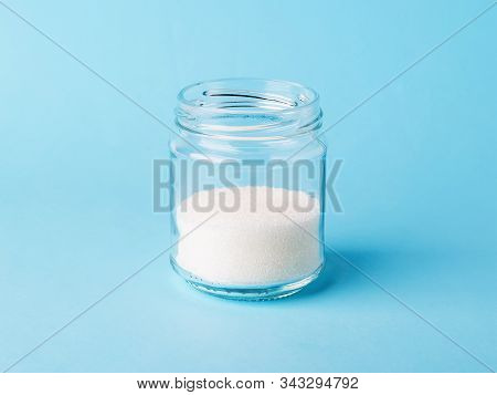 White Crystals Of Sugar In A Glass Bottle On A Pastel Blue Background. Simple Carbohydrate Or Monosa
