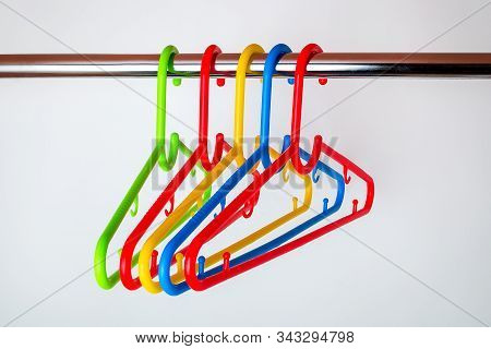 Five Multicolored Plastic Clothes Hangers On A Rod In The Closet. Set Of New Colorful Plastic Clothe