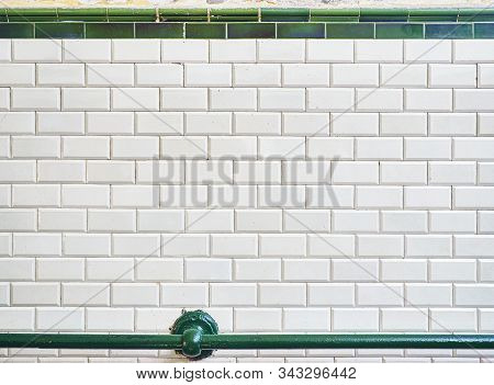 An Antique Wall Tiled With Metro Tiles Background Endowed With A Green Railing.