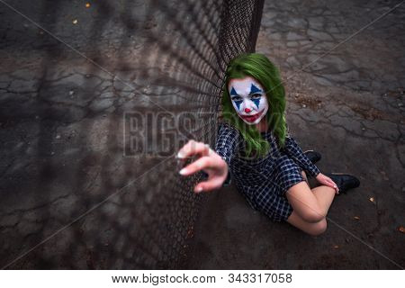 Greenhaired Girl In Chekered Dress With Joker Makeup Sitting Near Wire Mesh Fence On The Ground.