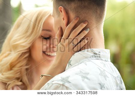 The Guy With The Girl Hugs And Kisses. A Romantic Date In A Pine Forest, Love Couple Of A Lovely Cou