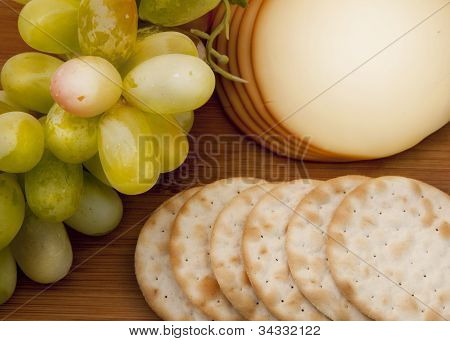 Grapes, cheese and crackers on wooden board