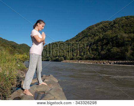 Young woman is practicing yoga in Warrior Pose (Virabhadrasana) pose at mountain lake
