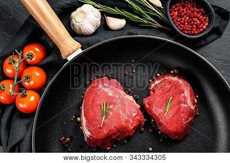 Filet Mignon Steak In A Frying Pan. Beef Tenderloin. Black Background. Top View