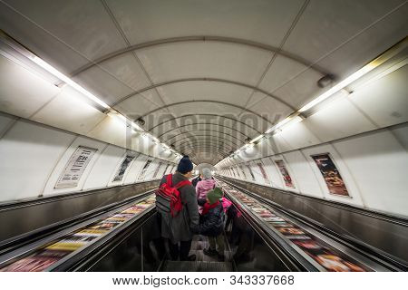 Prague, Czechia - November 2, 2019: People, A Family,  Going Down An Escalator With A Speed Blur Mov