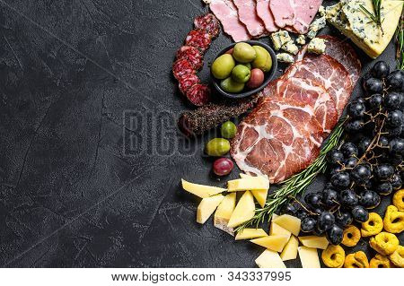 Typical Italian Antipasto With Prosciutto, Ham, Cheese And Olives. Black Background. Top View. Space