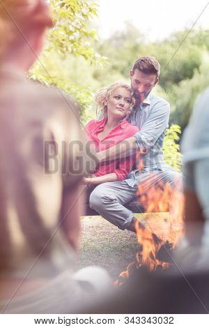 Young man embracing woman while sitting with friends at campsite in public park