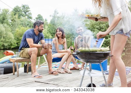 Low section of woman preparing food in barbecue grill with friends on pier