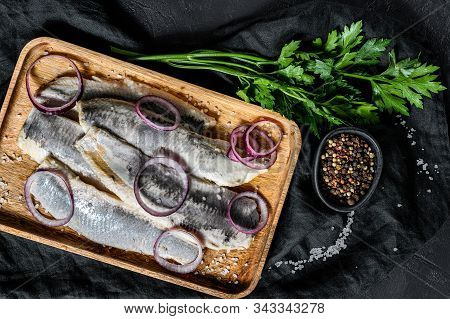 Marinated Herring Fillet With Pepper, Herbs And Red Onion. Black Background. Top View