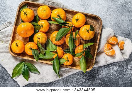 Fresh Mandarin Oranges Fruit Or Tangerines With Leaves In A Wooden Bowl. Gray Background. Top View