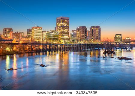 Richmond, Virginia, USA downtown skyline on the James River at twilight.