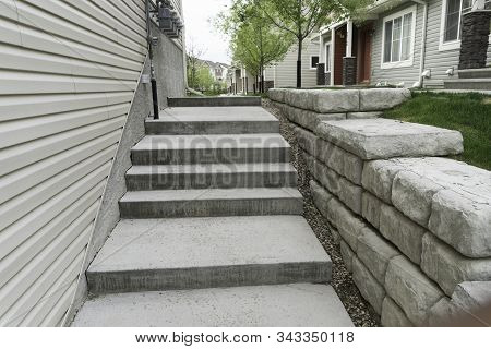 Walway In Apartment Block With Small Retaining Wall On Right Side