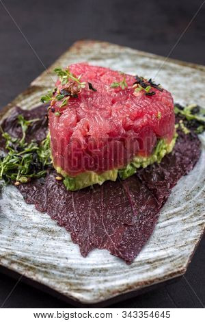 Gourmet fish tartar raw from tuna fillet with hashed avocado, umebashi and Japanese spice as closeup on modern design plate