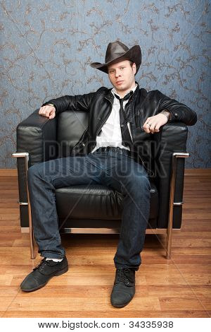 A Stylish Man Sitting In Leather Chair In Interiors