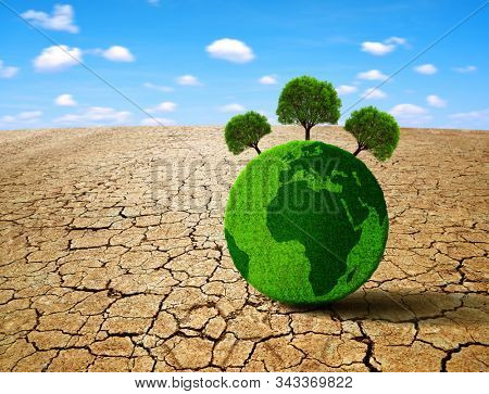 Green planet with trees in the dry landscape with cracked soil. Concept of change climate or global warming.
