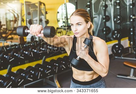 Working Out With Dumbbell Weights At The Gym.fitness Women Exercising Are Lifting Dumbbells. Fitness