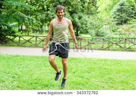 Man jumping a rope outdoors, cardio and stamina workout concept