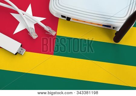 Togo Flag Depicted On Table With Internet Rj45 Cable, Wireless Usb Wifi Adapter And Router. Internet