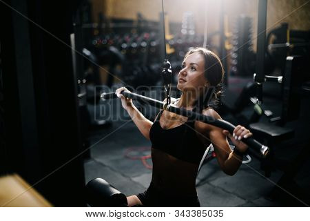 Athletic Young Woman Using Training Simulator For Pumping Back Muscles In Gym. Concept Of Healthy Li