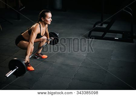 Athletic Woman Bodybuilder With Perfect Fitness Body Preparing To Lift The Heavy Barbell From The Fl