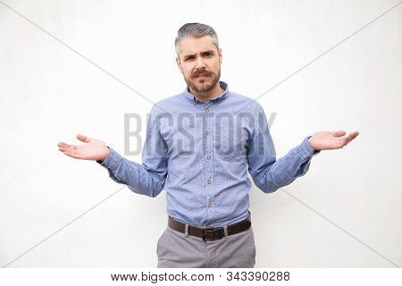 Puzzled Clueless Man Shrugging Shoulders, Looking Away. Grey Haired Young Man In Blue Casual Shirt P